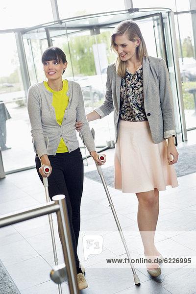Frau hilft einer behinderten Frau beim Gehen