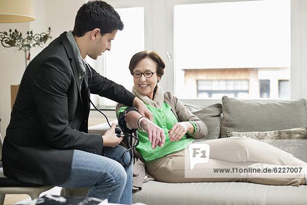 Männlicher Arzt bei der Untersuchung eines Patienten mit Stethoskop