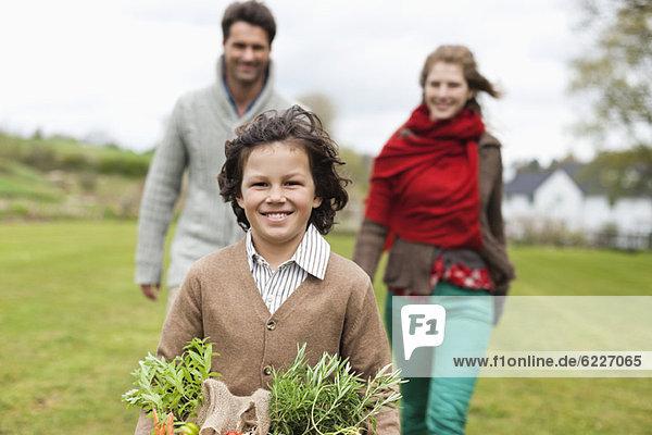 Porträt eines Jungen  der mit seinen Eltern auf einem Bauernhof einen Gemüsekorb hält.