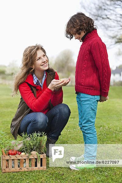 Frau zeigt ihrem Sohn Gemüse