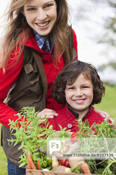 Mutter und Sohn mit einer Kiste mit einheimischem Gemüse