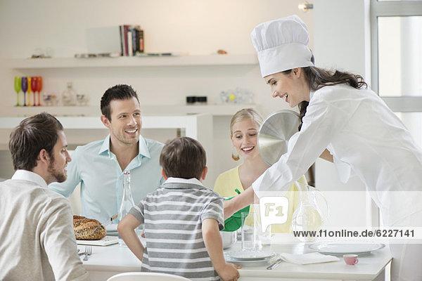 Frau serviert Mittagessen am Esstisch