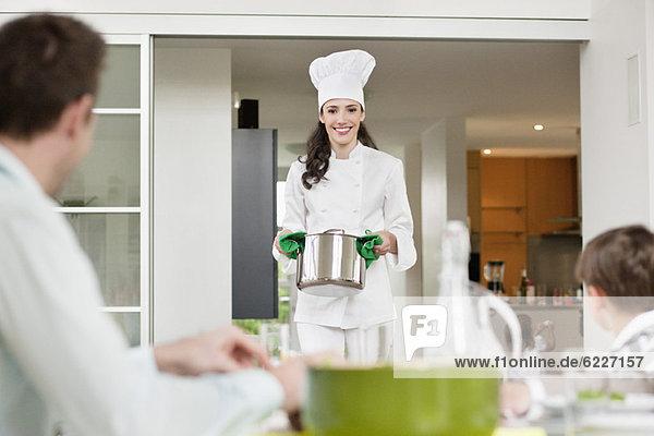 Frau  die ihrer Familie Essen serviert.