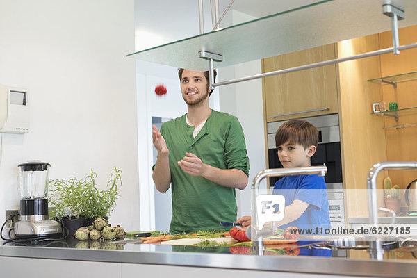 Mann und Sohn schneiden Gemüse in der Küche