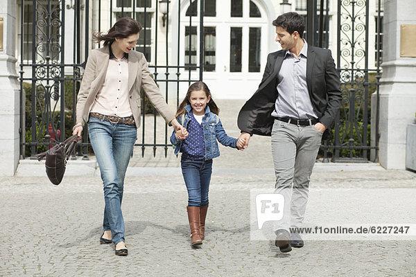 Porträt eines Mädchens  das mit seinen Eltern spazieren geht.