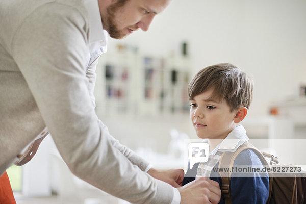 Mann bereitet seinen Sohn auf die Schule vor