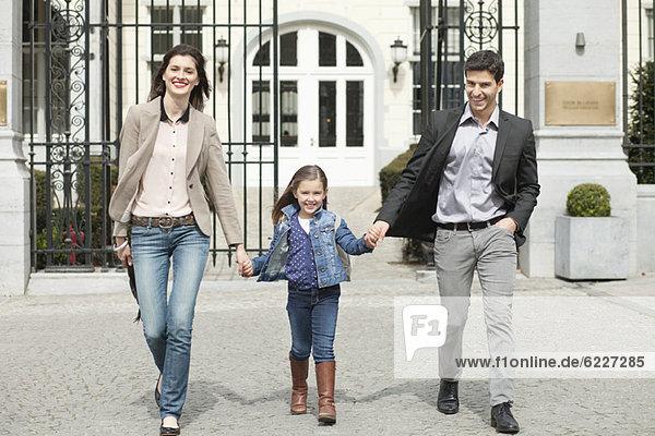Mädchen geht mit ihren Eltern spazieren