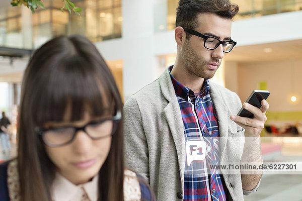 Modedesigner SMS auf dem Handy im Büro