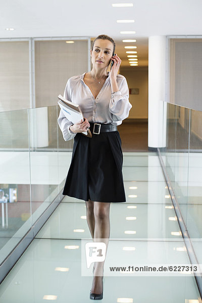 Businesswoman talking on a mobile phone in an office corridor