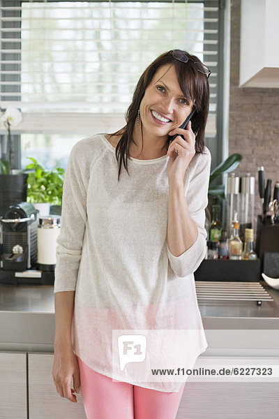 Woman talking on a mobile phone in a kitchen