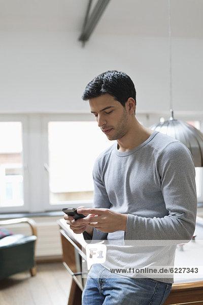 Mann lehnt sich mit dem Handy an einen Billardtisch
