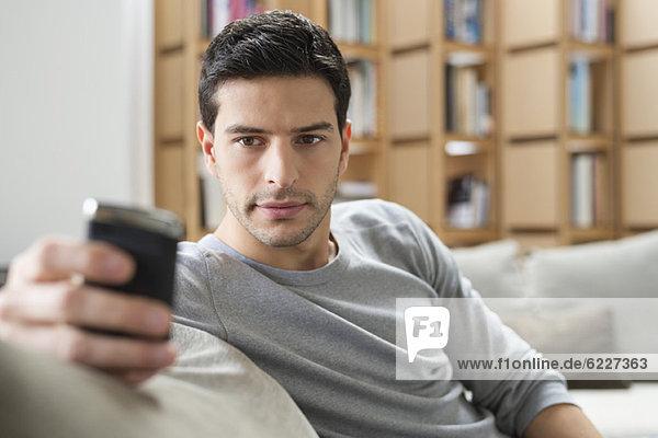 Mann  der sich auf einer Couch ausruht und ein Mobiltelefon benutzt.