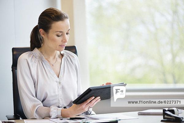 Geschäftsfrau mit einem digitalen Tablett im Büro