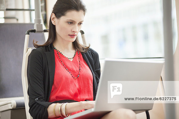 Frau  die in einem Bus reist und einen Laptop benutzt