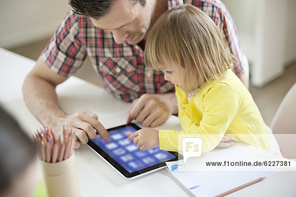 Mann  der seiner Tochter ein digitales Tablett beibringt.