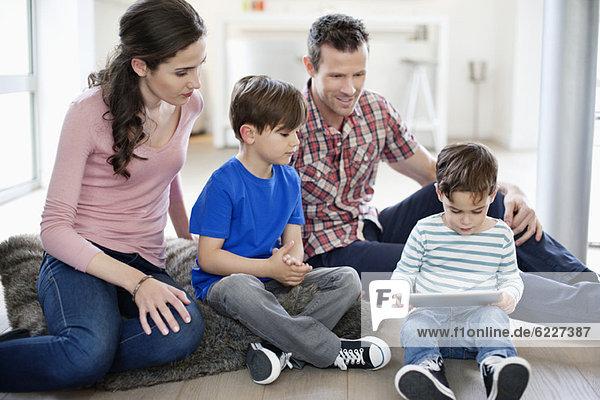 Eltern  die ihre Kinder mit Hilfe eines digitalen Tabletts betrachten