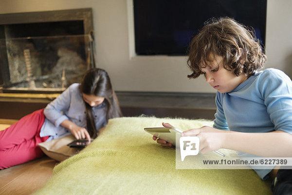 Junge und Mädchen mit elektronischen Geräten zu Hause