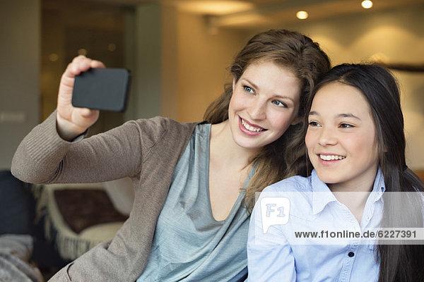 Frau und ihre Tochter machen ein Foto von sich selbst mit einem Fotohandy.