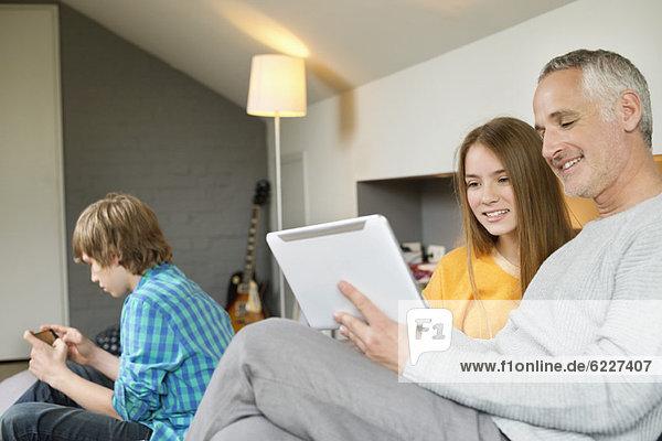 Mann  der ein digitales Tablett mit seiner Tochter zu Hause benutzt.
