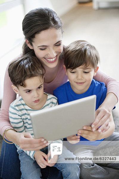 Frau zeigt ihren Kindern ein digitales Tablett