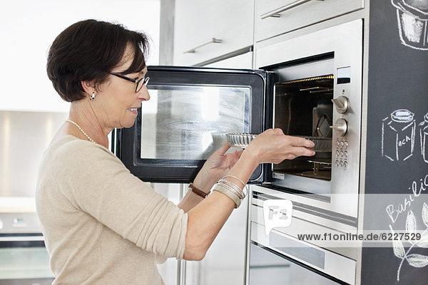 Ältere Frau stellt ein Tablett in den Ofen