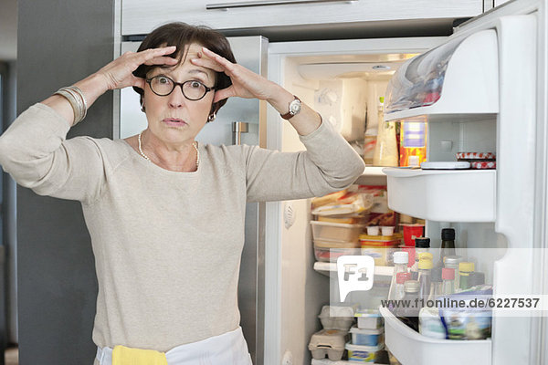 Portrait of an elderly woman looking shocked in front of a refrigerator