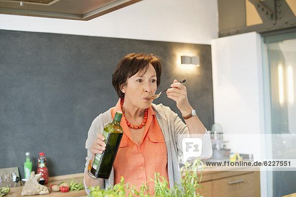 Ältere Frau schmeckt Olivenöl in der Küche