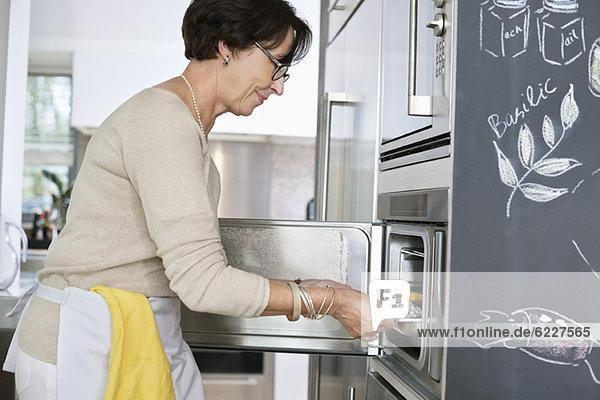 Ältere Frau  die ein Tablett mit Meeresfrüchten in den Ofen stellt.