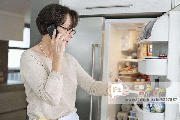 Ältere Frau überprüft Lebensmittel im Kühlschrank und telefoniert mit dem Handy.