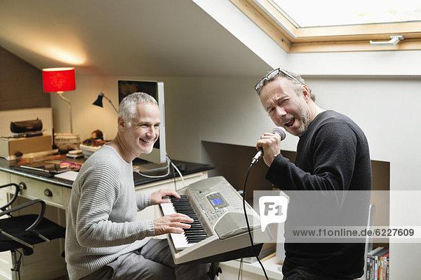 Zwei männliche Freunde  die Klavier spielen und singen.