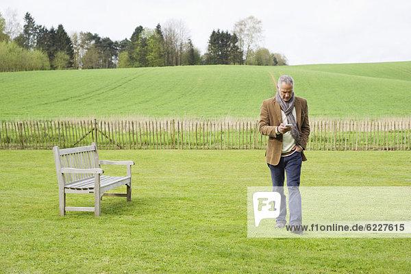 Ein Mann  der ein Mobiltelefon auf einem Feld benutzt.