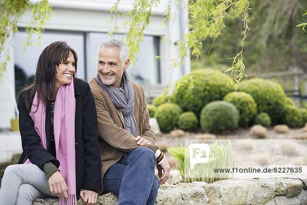Romantisches Paar im Garten sitzend und lächelnd