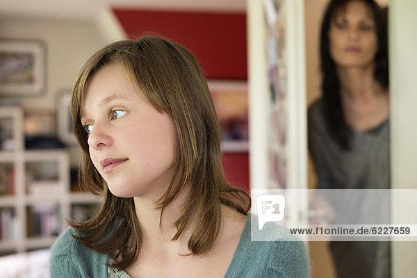 Frau beobachtet ihre Tochter hinter der Tür im Schlafzimmer