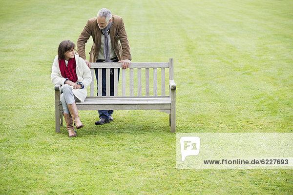 Mann sitzend mit seiner Tochter auf einer Bank im Park