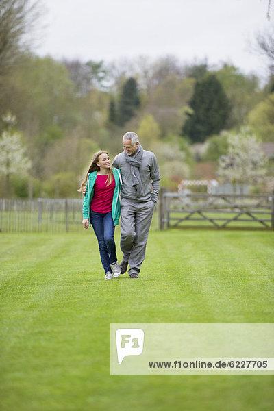Ein Mann  der mit seiner Tochter auf einem Feld spazieren geht.