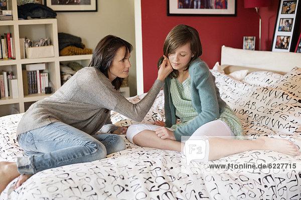 Frau tröstet ihre traurige Tochter im Schlafzimmer