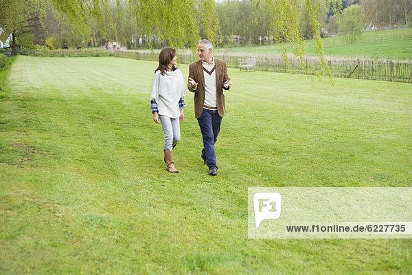 Mann diskutiert mit seiner Tochter beim Spaziergang im Park