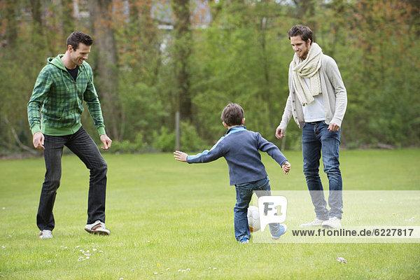 Junge spielt Fußball mit zwei Männern im Park