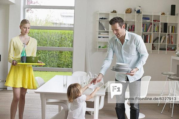 Frau serviert Essen mit ihrem Mann und ihrer Tochter  die Teller am Esstisch halten.