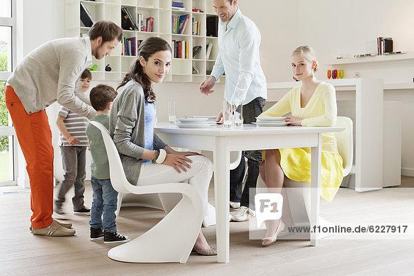 Familie am Esstisch mit Gästen