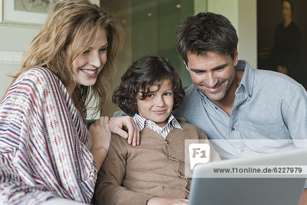 Junge mit Laptop bei seinen Eltern zu Hause