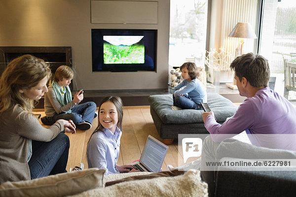 Familie mit elektronischen Geräten im Wohnzimmer