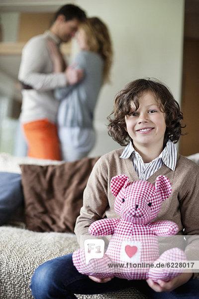 Junge sitzend mit einem Spielzeug mit seinen Eltern  die im Hintergrund romantisch tanzen