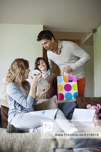 Mann mit seinem Sohn  der seiner Frau zu Hause ein Überraschungsgeschenk macht.