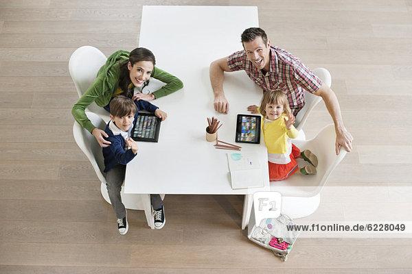 Hochwinkelansicht des Paares mit seinen Kindern am Arbeitstisch