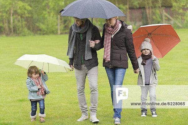 Familie mit Regenschirmen im Park
