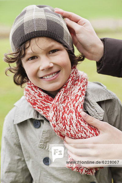 Woman putting on warm clothing on her son