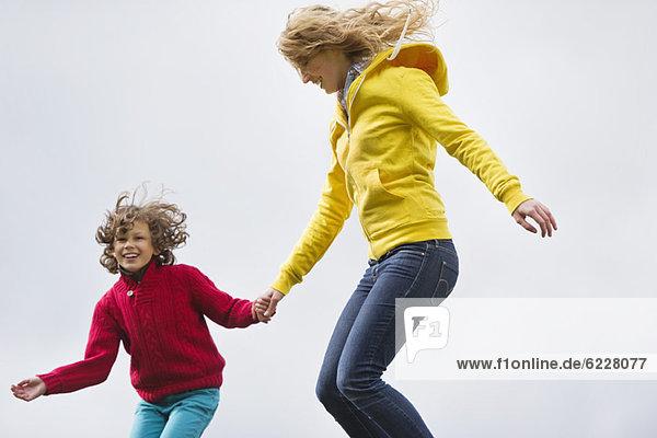 Frau mit ihrem Sohn springt und lächelt