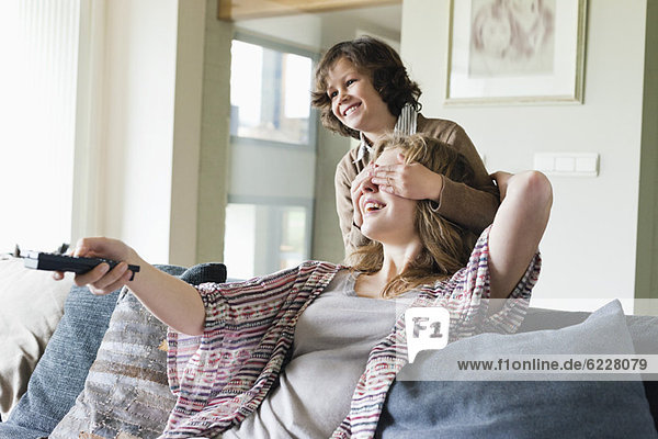 Junge bedeckt die Augen seiner Mutter beim Fernsehen