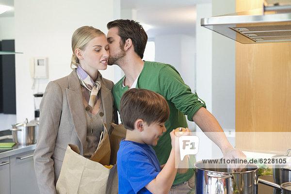 Mann  der seine Frau küsst  die vom Einkaufen zurückkehrt  und Sohn  der in der Küche kocht.